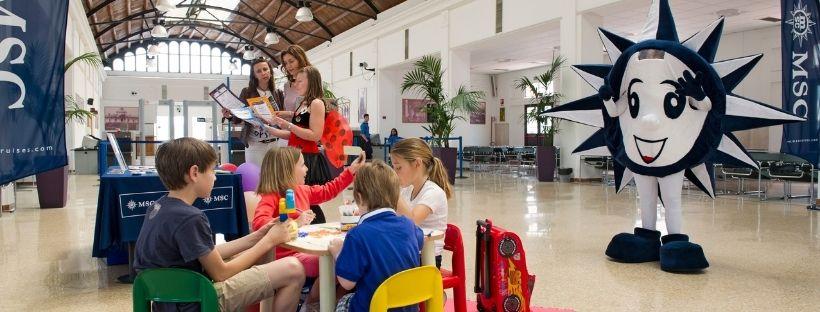 Des enfants à une table et la mascotte MSC en fond