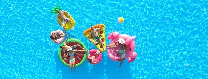 Amis chacun dans leurs bouées gonflables au milieu d'une piscine