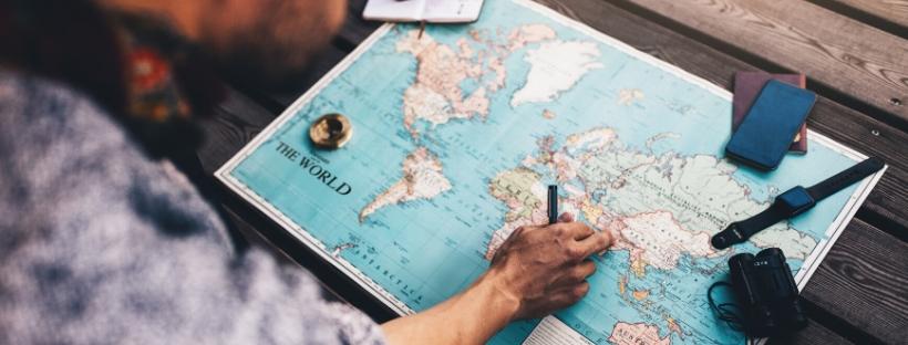 Une personne qui tient un stylo, sur une carte du monde