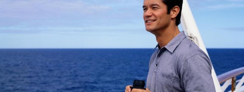 Homme de profil, sur un pont, regardant vers la mer