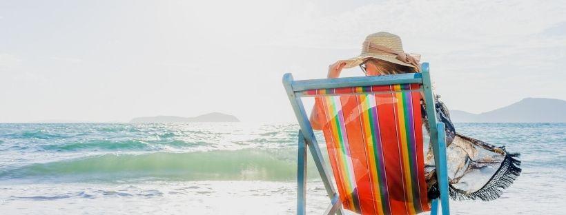 femme sur un transat sur la plage face à la mer