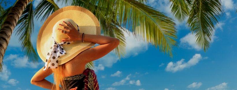 Femme de dos avec un grand chapeau regardant la mer sur une plage