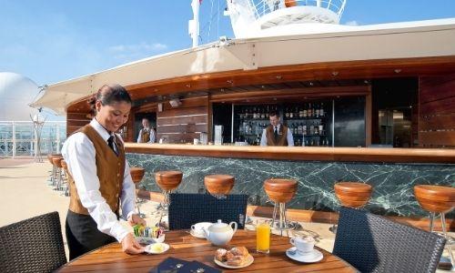 jeune femme qui sert des petites assiettes sur une table d'un bar sur le pont d'un bateau
