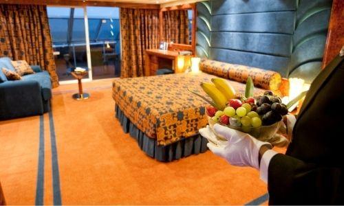 majordome au premier plan qui apporte une corbeille de fruits dans une suite du MSC Yacht Club
