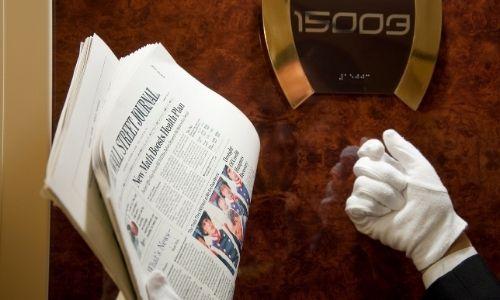 main d'un majordome qui frappe à la porte d'une suite, tenant dans ses mains des journaux