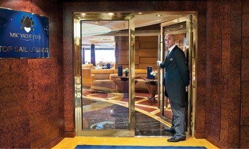 membre de l'équipe du MSC Yacht Club qui vous propose d'entrer dans le Top Sail Lounge d'un bateau MSC