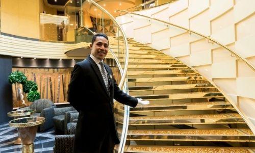 jeune homme qui tend la main vers un grand escalier montant, comme pour nous inviter à monter