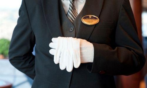 majordome en uniforme qui porte un gant avec l'autre dans sa main