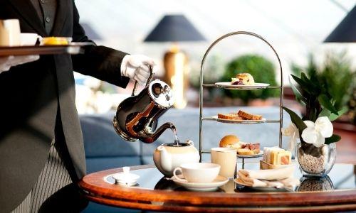 majordome qui sert le thé sur une table dressée tout en portant un plateau dans sa main droite