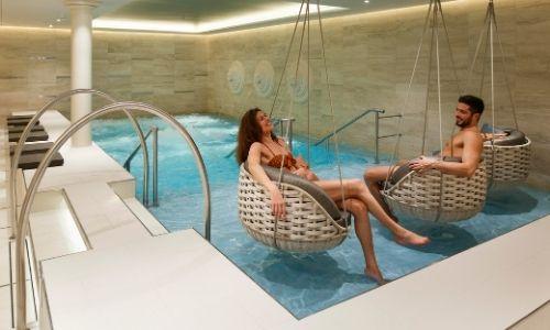 un jeune couple qui se détend dans des fauteuils en osier au dessus d'une petite piscine dans un spa