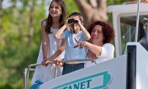 Deux enfants et leur maman qui observent tous trois en direction du même point, le petit garçon observant depuis des jumelles