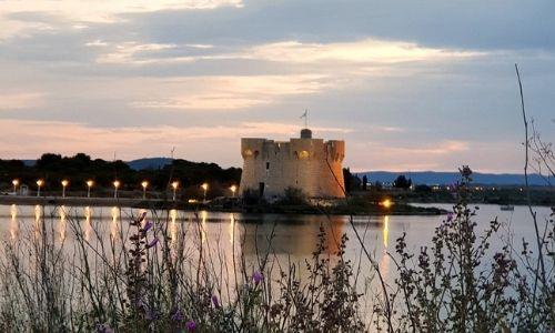 grand lac photographié à l'aube avec à l'arrière-plan un château illuminé