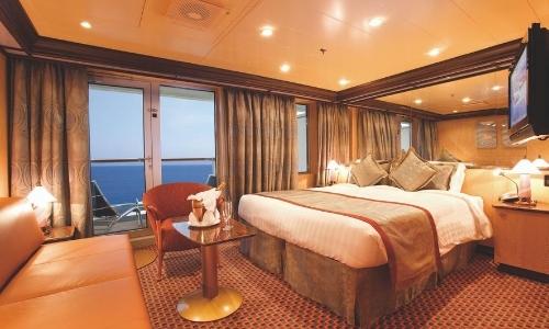 Vue de l'intérieur d'une chambre sur un navire de croisière avec grand lit, fauteuil, canapé, TV, et fenêtres avec vue sur la mer