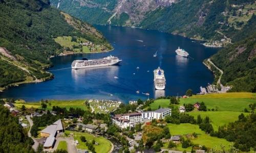 Vue sur un fjord en Norvège avec verdure, bateaux de croisière, habitations, ambiance nature