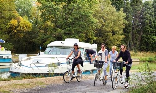 famille qui se balade à vélo à côté d'un bateau sans permis sur le bord d'une rivière