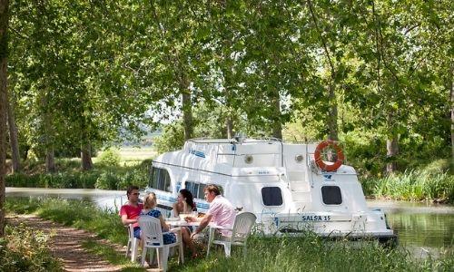 famille qui profite d'un repas sous les arbres sur le bord d'un fleuve à côté de leur péniche