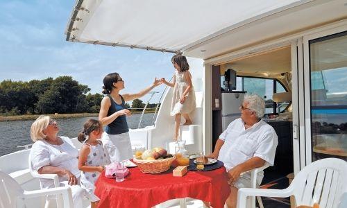 famille sur la terrasse d'une péniche qui profite du soleil