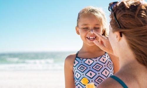 jeune maman qui met de la crème solaire à sa petite fille tout sourire