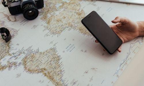 carte du monde posée avec un téléphone tenu dans la main d'une personne