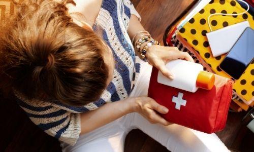 jeune femme vue de haut qui tiens une trousse à pharmacie et une crème solaire dans ses main