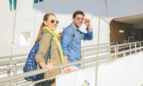 Homme et femme embarquant au sein d'un bateau de croisière avec leurs sacs à dos