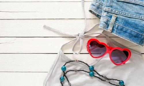Short en jean, débardeur blanc, collier, et lunettes de soleil en forme de coeur