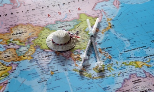 Carte du monde axée sur l'Asie, avec chapeau sur la carte et flacons de vaccins ) côté