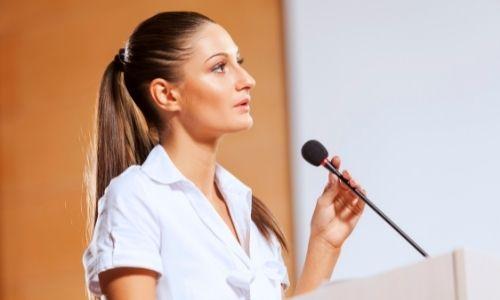 femme qui donne une conférence avec un micro devant elle