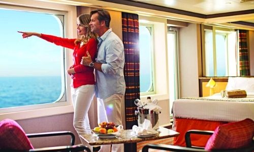 Couple dans leur cabine extérieure, la femme pointe du doigt la mer et l'homme la tiens juste derrière