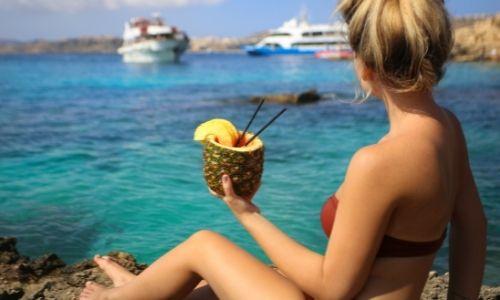 Jeune femme devant la mer qui tient dans ses mains un cocktail ananas