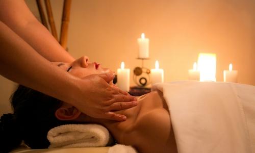 Une femme vue de profil se faisant masser la nuque au spa avec des bougies en arrière plan