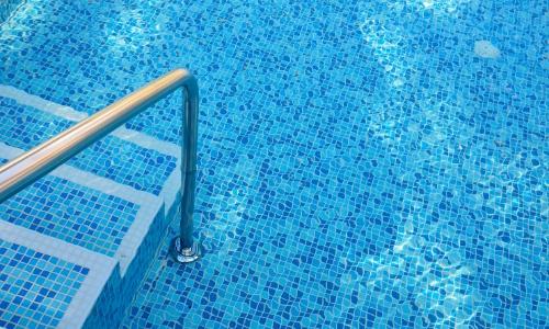 Vue sur une piscine, avant de rentrer dans l'eau par des marches