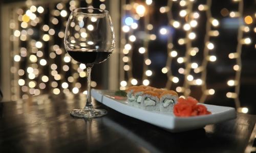 Verre de vin rouge avec une assiette de sushis à côté, dans une ambiance zen