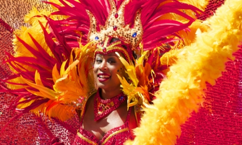 Femme déguisée pour le carnaval de Rio avec couronne et plumes rouges et jaunes