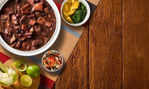 Photo du plat traditionnel national : la feijoada à base de viande de porc et haricots noirs, avec accompagnements et boisson