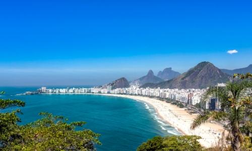 Vue sur la vaste plage de Copacabana à Rio de Janeiro au Brésil avec sable blanc, habitations tout le m-long et montagnes en arrière-plan