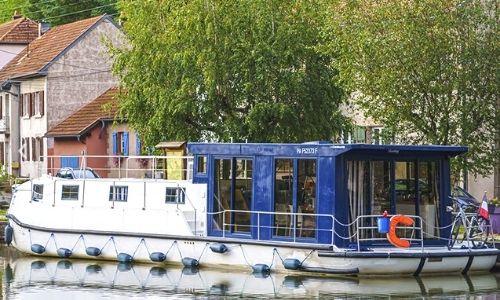 bateau les Canalous de la flotte Electrique sur l'eau près d'un village