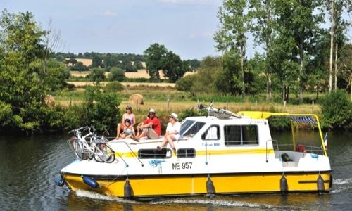 Famille sur un bateau jaune les Canalous sur un canal en France