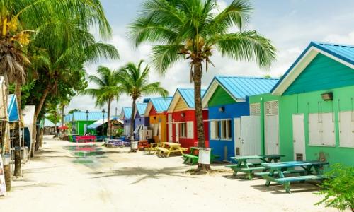 Petites maisons colorées sur le sable aux Caraïbes avec palmiers