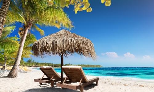 Vue sur une plage des Caraïbes avec mer turquoise, sable blanc, ciel bleu, palmiers et transats
