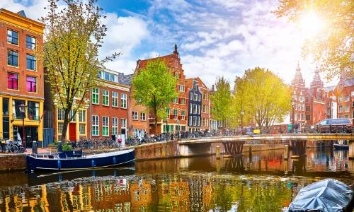 Vue sur Amsterdam avec canal, maisons colorées et arbres