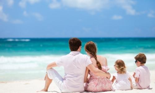 Vue sur une famille de 4 personnes de dos assises sur le sable blanc aux Caraïbes