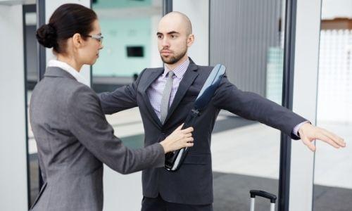 jeune femme qui fait le contrôle d'objets dangereux ou interdit sur un jeune homme