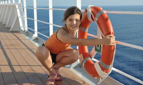 etite fille accroupie qui tient dans ses mains la bouée de sauvetage du bateau de croisière
