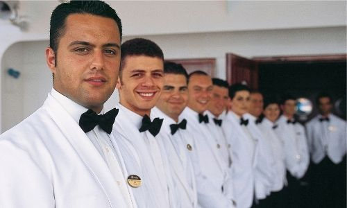 membres de l'équipage d'un bateau alignés, en costume blanc et noeud papillon noir avec le sourire