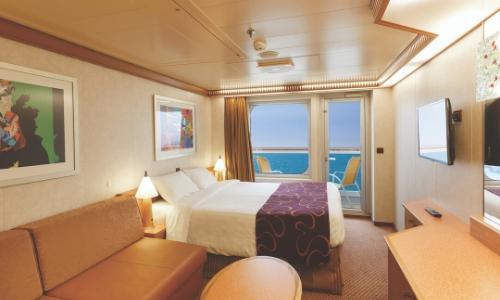 Vue sur une cabine avec balcon, lit double, bureau, canapé