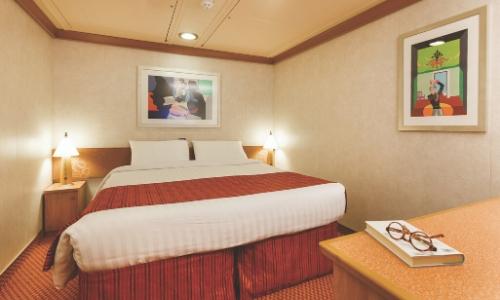 Vue dans une cabine intérieure avec lit double, tables de chevet, petit bureau