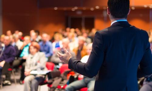 Dans une salle de conférence, personne assises, présentateur debout devant