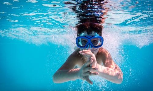 Enfant sous l'eau, dans la piscine avec masque