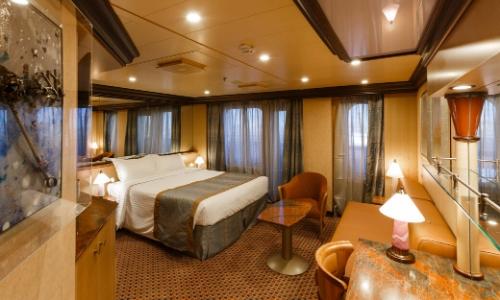 Intérieur d'une suite avec grand lit, fenêtres, canapé, table, fauteuil